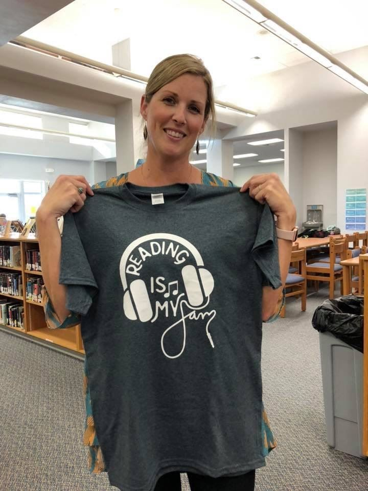 Media specialist holding up t-shirt for sale
